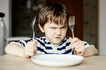 38654425 - furious little boy waiting for dinner. holding a spoon and fork in the hand